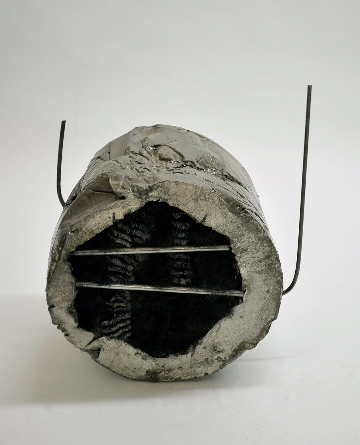 Hole with some bars, 2010, cast concrete, steel, faux fur, resin, black wig, 25 x 21 x 15 inches